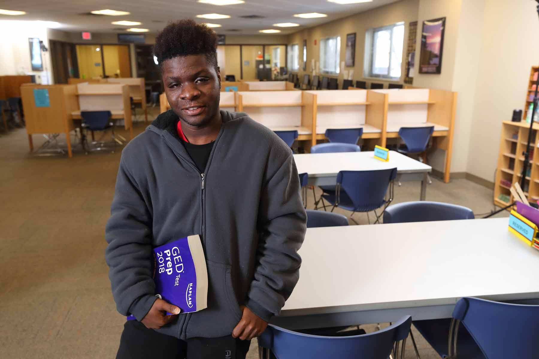 Student leaning on table with GED Studyguide