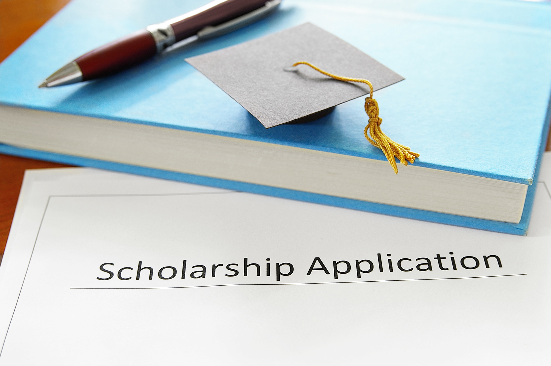 Scholarship application form next to book
