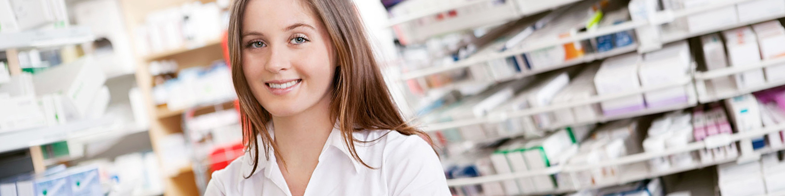 Young woman in posing in a pharmacy in front of rows of pills